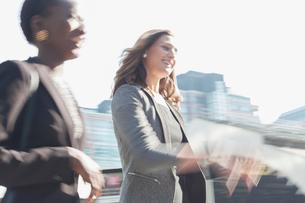 Smiling corporate businesswomen walking outdoorsの写真素材 [FYI02171694]