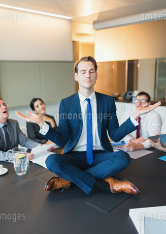 Colleagues watching zen-like businessman meditating in lotus position on conference tableの写真素材 [FYI02171736]