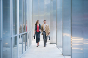 Corporate businessman and businesswoman walking along modern buildingの写真素材 [FYI02171755]