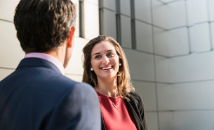 Corporate businesswoman smiling and talking to businessmanの写真素材 [FYI02171771]