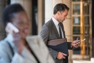 Corporate businessman using digital tablet outdoorsの写真素材 [FYI02171784]