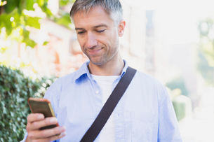 Businessman texting with cell phone outdoorsの写真素材 [FYI02171803]