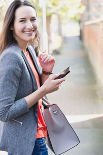 Portrait smiling businesswoman with cell phone on sidewalkの写真素材 [FYI02171809]