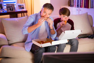 Father and son eating pizza and watching TV in living roomの写真素材 [FYI02171816]