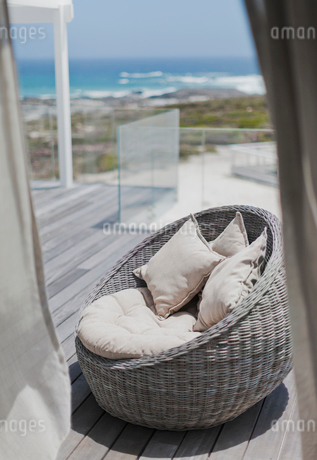 Wicker seat with cushions on sunny beach house deck with ocean viewの写真素材 [FYI02171826]