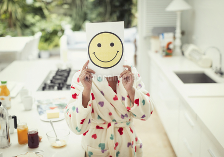 Portrait of women holding smiley face printout over face in kitchenの写真素材 [FYI02171848]