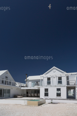 White house and swimming pool under sunny blue skyの写真素材 [FYI02171858]