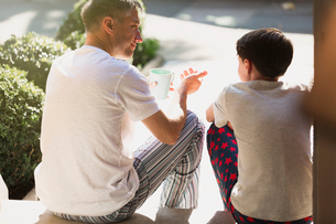 Father with coffee talking to son on front stoopの写真素材 [FYI02171883]