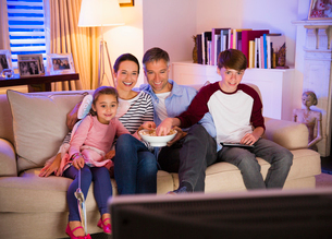 Family eating popcorn and watching TV in living roomの写真素材 [FYI02171907]