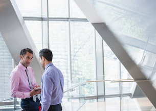 Corporate businessmen with digital tablet talking in modern office lobbyの写真素材 [FYI02171944]