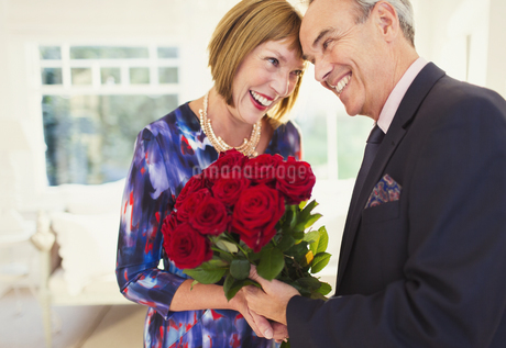 Affectionate well-dressed mature couple with rose bouquetの写真素材 [FYI02171953]