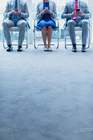 Business people with cell phones waiting in a rowの写真素材 [FYI02171954]
