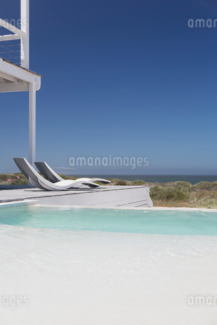 Modern lounge chairs at poolside with ocean view under sunny blue skyの写真素材 [FYI02171992]