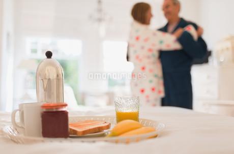 Mature couple in bathrobes dancing behind breakfast in bedの写真素材 [FYI02172007]