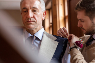 Tailor fitting businessman for suit in menswear shopの写真素材 [FYI02172019]