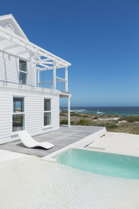 White beach house and swimming pool with ocean view under sunny blue skyの写真素材 [FYI02172039]