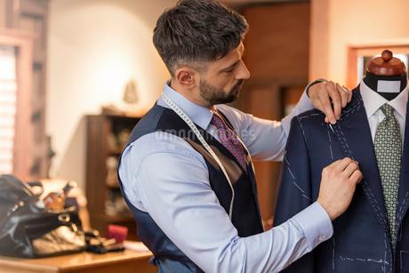 Tailor adjusting suit on dressmakers model in menswear shopの写真素材 [FYI02172049]