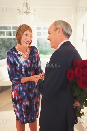 Well-dressed husband surprising wife with rose bouquetの写真素材 [FYI02172051]