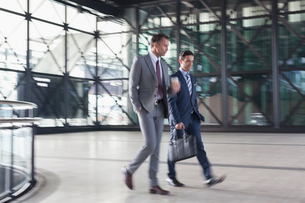Corporate businessmen walking in modern lobbyの写真素材 [FYI02172066]