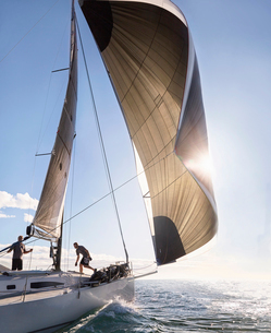 Wind pulling sail on sailboat on sunny oceanの写真素材 [FYI02172075]