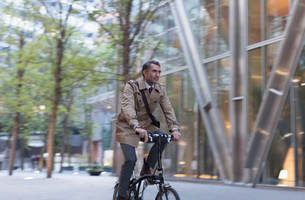 Corporate businessman riding bicycle outside modern buildingの写真素材 [FYI02172097]
