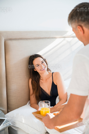 Wife smiling at husband serving breakfast in bedの写真素材 [FYI02172121]