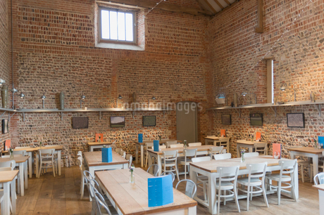 Tables in vacant restaurant with brick walls and vaulted ceilingの写真素材 [FYI02172150]