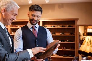 Worker showing dress shoes to businessman in menswear shopの写真素材 [FYI02172153]