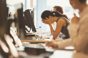 Stressed businesswoman with head in hands at office deskの写真素材 [FYI02172156]