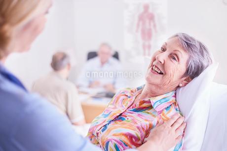 Doctor comforting smiling senior woman at checkupの写真素材 [FYI02172166]
