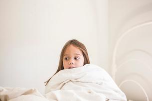 Toddler girl sitting up in bed under duvetの写真素材 [FYI02172192]