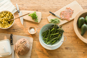 Overhead view lox, asparagus, pasta, bread and butter on dining tableの写真素材 [FYI02172196]