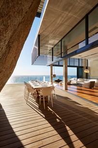 Modern luxury dining table on sunny patio with ocean viewの写真素材 [FYI02172197]