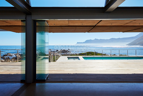 Modern luxury home showcase patio overlooking swimming pool and sunny ocean viewの写真素材 [FYI02172201]