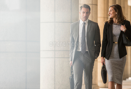 Corporate businessman and businesswoman walking and talking in cloisterの写真素材 [FYI02172202]