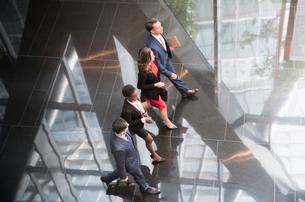Corporate business people walking in a row in modern office lobbyの写真素材 [FYI02172230]