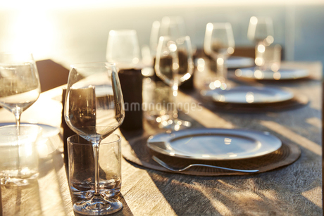 Sun shining over placesettings on wooden tableの写真素材 [FYI02172252]