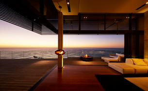 Fire pit and hanging fireplace on modern luxury patio with sunset ocean viewの写真素材 [FYI02172264]
