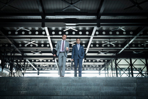 Corporate businessmen with coffee descending modern stairsの写真素材 [FYI02172266]