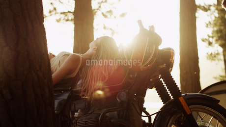Young woman laying on motorcycle under sunny treesの写真素材 [FYI02172283]