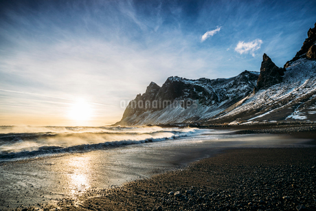 Sun setting over tranquil beach and snowy mountain, Icelandの写真素材 [FYI02172292]