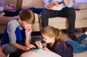 Brother and sister sharing digital tablet in living roomの写真素材 [FYI02172295]