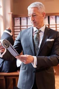 Businessman browsing fabric in menswear shopの写真素材 [FYI02172302]
