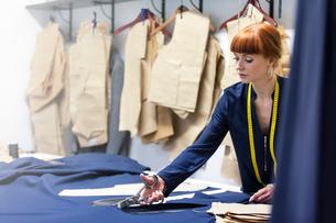 Female tailor cutting fabric in menswear workshopの写真素材 [FYI02172328]
