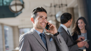 Smiling corporate businessman talking on cell phoneの写真素材 [FYI02172334]