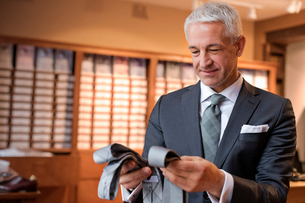 Businessman browsing ties in menswear shopの写真素材 [FYI02172337]