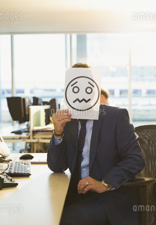 Portrait of businessman holding frowning face printout over his face in officeの写真素材 [FYI02172340]