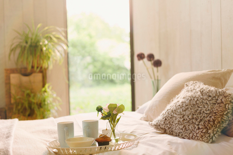 Breakfast tray with flower on bed in tranquil bedroomの写真素材 [FYI02172349]