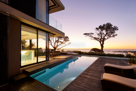 Modern luxury home showcase patio and swimming pool with sunset ocean viewの写真素材 [FYI02172350]