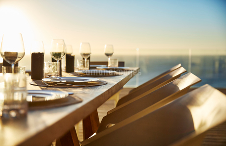 Sunset behind placesettings on luxury patio dining tableの写真素材 [FYI02172383]